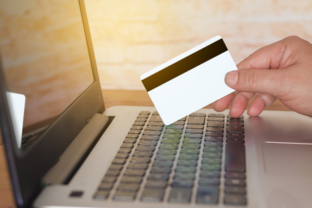 Hand holding credit card on laptop for online shopping concept.