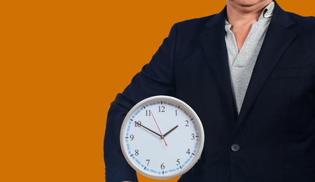 Business man hold a analog clock ,business concept.
