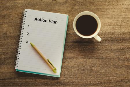 Texto del plan de acción en nota de libro con taza de café, bolígrafo.