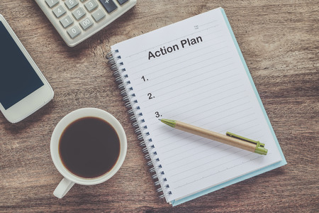 Action Plan text on book note with cup of coffee, pen.