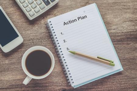 Testo del piano d'azione sulla nota del libro con una tazza di caffè, penna.