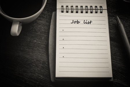 Job list text on book note with cup of coffee, pen. Imagens