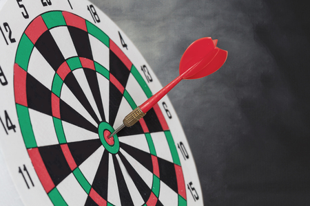 Dart arrow hitting in bullseye on dartboard with black background.