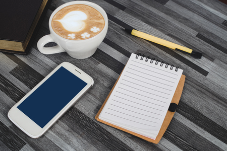 Book note ,smart phone and coffee on office table . Stock fotó