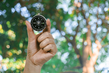 Compass in hand with nature background ,traveler concept. 写真素材
