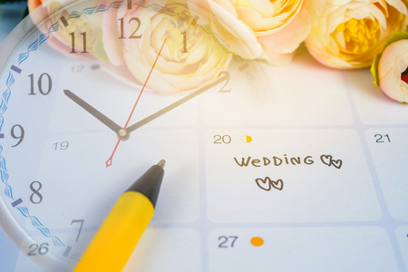 Word Wedding to Reminder Wedding day in calendar planning and pen with clock