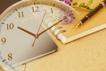 organisateur personnel ou planificateur avec stylo plume sur horloge