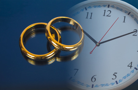 Wedding ring on screen of smart phone and clock. love concept.