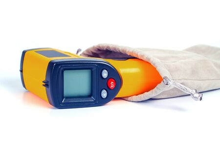 Yellow Infrared thermometer gun used to measure temperature  on white background.