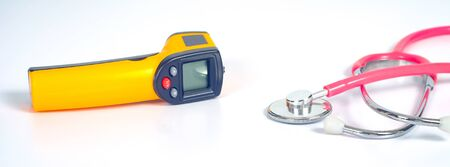 Yellow Infrared thermometer gun used to measure temperature with stethtoscope on white background.