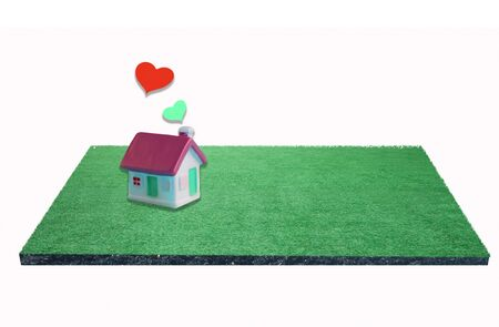 miniature house with heart sign on green field ,love family    concept.