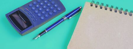 Book note and calculator on color background. Stock Photo