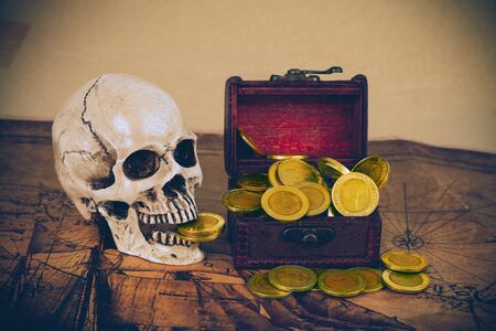 skull with gold coin in old box on old map.