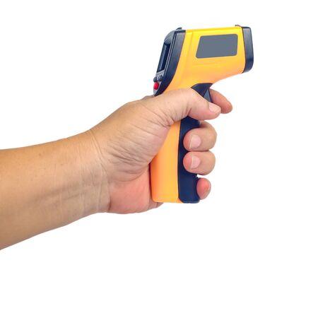 Pistola de termómetro infrarrojo amarillo en la mano utilizada para medir la temperatura sobre fondo blanco.