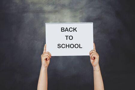 Woman hands holding high a post card that says BACK TO SCHOOL against a blackboard.