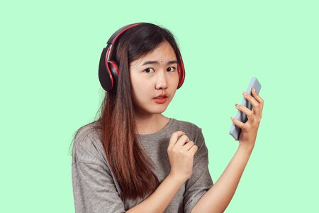 young woman wearing headset enjoying new audio tracks playing in    smartphone. Stock Photo
