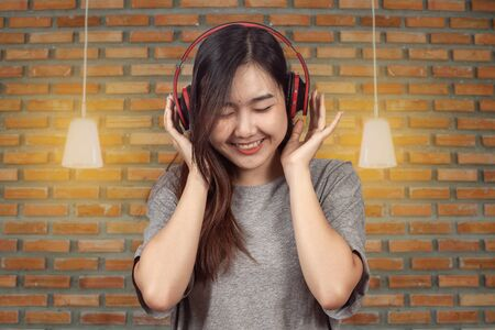 young woman wearing headset enjoying new audio tracks playing in smartphone.