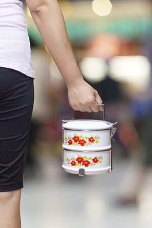 Hand holding Food carrier or tiffin food container on background.