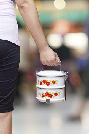 Main tenant un transporteur de nourriture ou un récipient de nourriture tiffin sur fond. Banque d'images