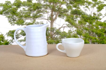White coffee cup and jar on wood table with nature background.