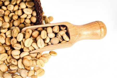 Fresh Raw coffee beans in wood spoon on background. Stock Photo