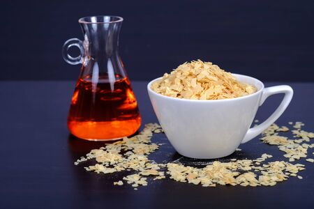 Cornflakes in coffee cup on a dark wooden background and copy    space.