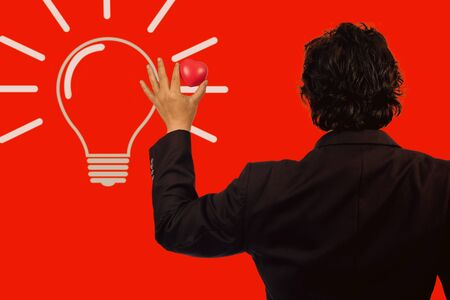Business man holding red heart ball with light bulb.idea concept. Stockfoto