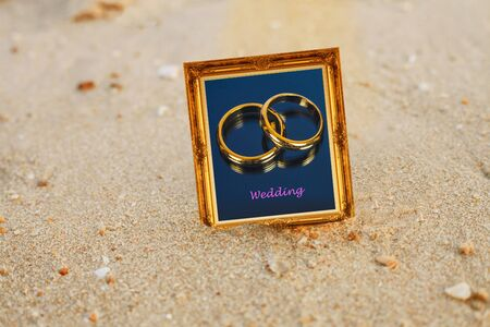 Golden wedding ring in vintage gold picture frame on sand beach.
