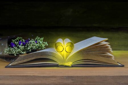 Still life Heart sign with wedding ring on text book on wood table background. Zdjęcie Seryjne