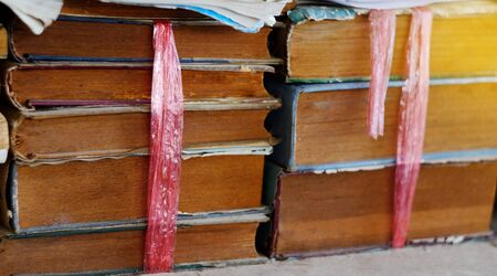 Stack of old and used books or text books lying on wooden. Stock Photo
