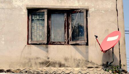 Red satlelite dish on old wall behind windows. Foto de archivo