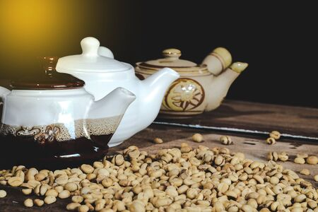 Traditional Teapot with raw coffee beans on wood table.