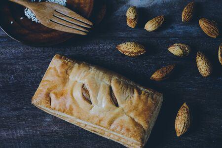 Bread pie apple pocket pie with almond on wood background.