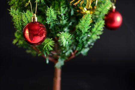 Rote Kugelweihnachtsdekoration auf grüner Kiefer, Weihnachtshintergrund.