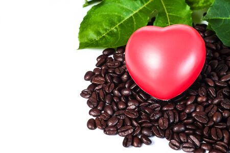 Red heart ball on fresh coffee beans on white background .