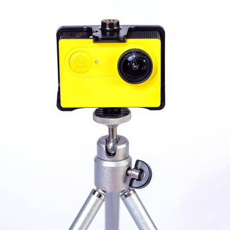 Action camera on mini tripod with white background.