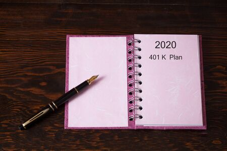 2020 plan with 401K plan on Book note and fountain pen on wood table.