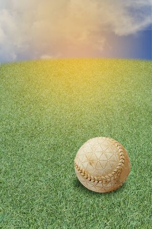 A old baseball lies in the grass yard waiting to be picked up. Concept  playing baseball on out door.