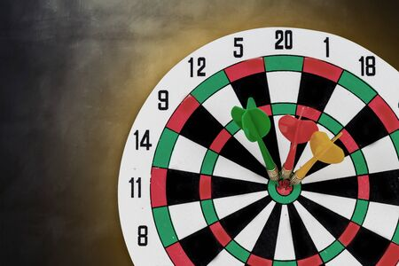Dart arrow hitting in bullseye on dartboard with light background on wall.