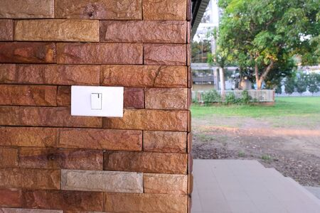 Power plug and swich on or off on old brick wall.