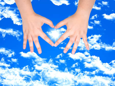 woman Hands making heart with the sun inside over blue sky background  photo
