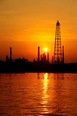 Silhouette oil refinery at sunrise