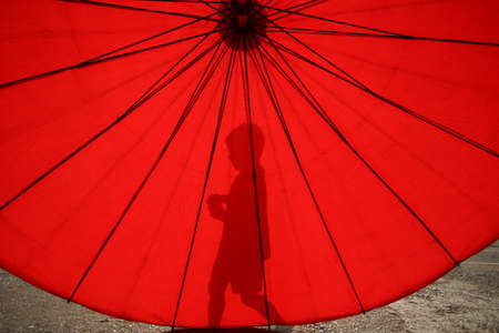 Silhouette of a little boy with red umbrella during sunset.