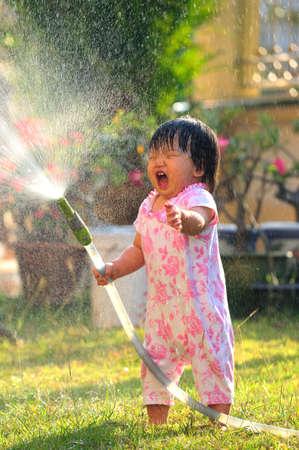 moisten: Happy girl pours water from a house in summer season