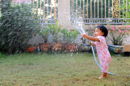 moisten: Happy girl pours water from a house in summer