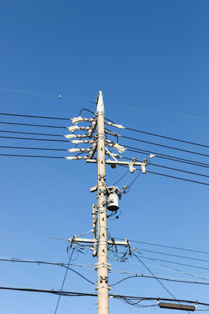 power cables: Electrical post with power line cables., against blue sky