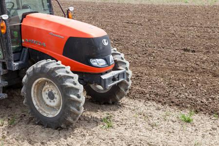 cultivator: NAGOYA, JAPAN - April 16, 2016: Farmer in tractor preparing land for sowing.  Farmer in tractor preparing land with seedbed cultivator. Editorial