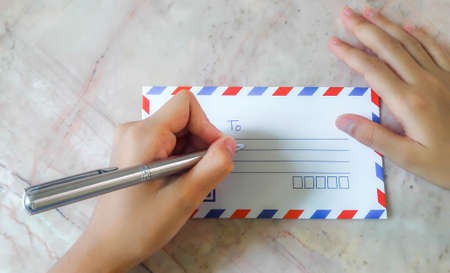 airmail: The girl hand writing on airmail envelope, Letter to.