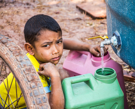 supplicate: Nakhon Ratchasima,THAILAND - March 4: Unidentified  Asian boy Saving water for use it in the family in summer no March 4,2016 in Khong district,Nakhon Ratchasima,THAILAND.