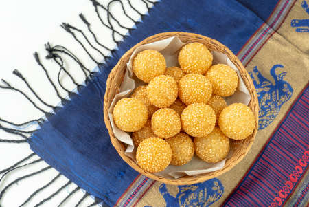 many kind of thai dessert, sesame balls in a wooden basket ,glutinous rice flour and stuffed inside a green bean paste with sesame seeds , Stockfoto - 110353342